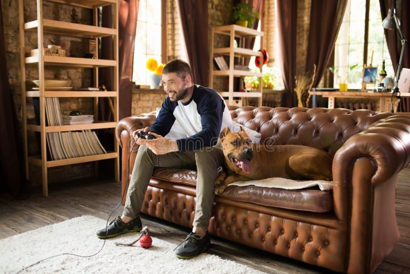 Tipo bello che si siede sul sofà con il suo cane, giocante video gioco immagine stock