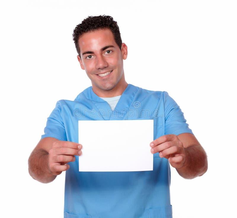 Tipo bello dell'infermiere che tiene una carta bianca fotografia stock
