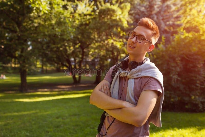 Tipo bello dell'istituto universitario che raffredda nel parco della città universitaria di primavera Lo studente felice dell'uom fotografie stock