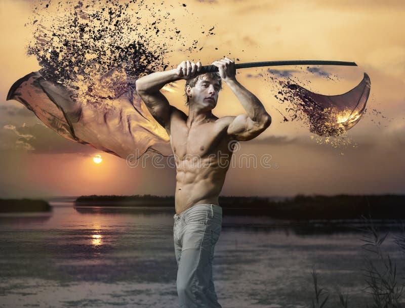 Tipo bello muscolare con la spada al tramonto immagine stock libera da diritti