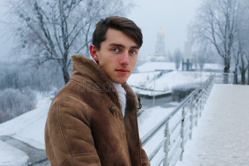 Tipo bello sul ponte durante l'inverno fotografia stock libera da diritti