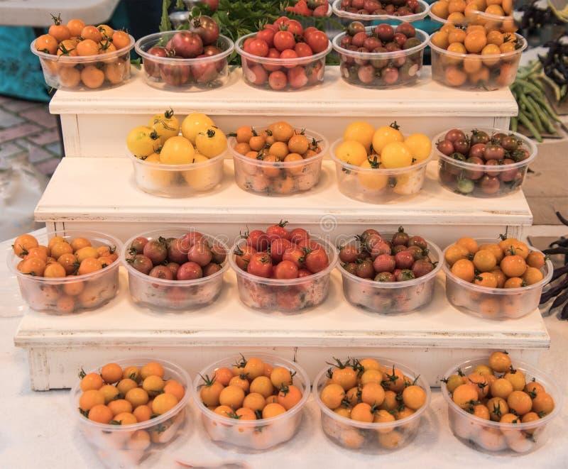 Tipo bianco esposizione di punto di chiari recipienti di plastica che tengono i vari colori dei pomodori ciliegia fotografie stock libere da diritti