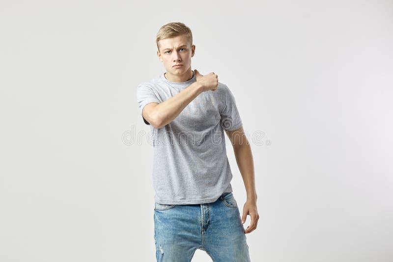 Tipo biondo aggressivo vestito in una maglietta bianca e nei supporti dei jeans sui precedenti bianchi nello studio fotografia stock libera da diritti