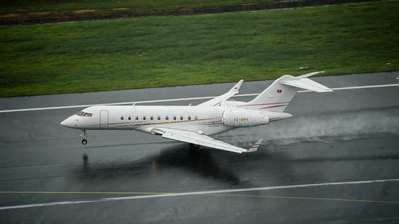 Tipo bombardeiro 5000 globais do jato privado que aterram na pista de decolagem molhada em foto de stock royalty free