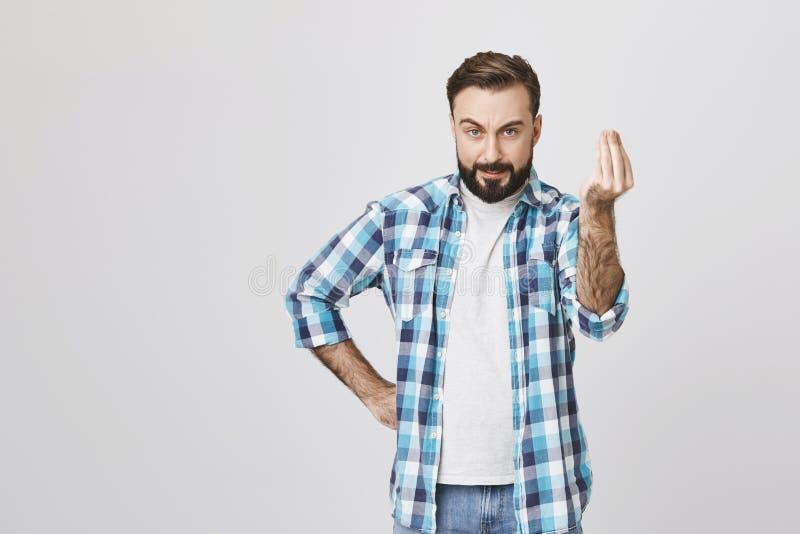 Tipo caucasico attraente che sembra pazzo ed arrabbiato, tenendo mano sulla vita mentre mostrano ottenga al gesto del punto con fotografia stock libera da diritti