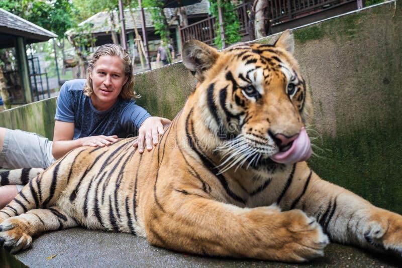 Tipo che abbraccia tigre fotografia stock