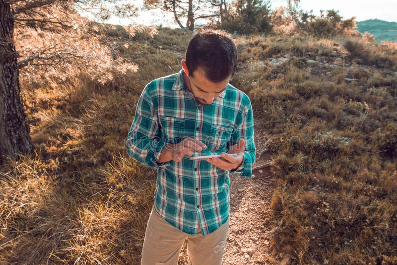 Tipo che esamina il suo telefono cellulare nel campo fotografia stock