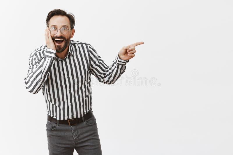 Tipo che pettegola circa il compagno di classe con gli amici durante la riunione dell'istituto universitario, ridendo sopra la pe fotografia stock libera da diritti