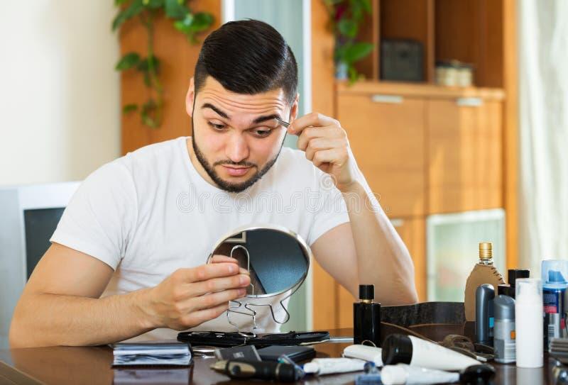 Tipo che rimuove i capelli del sopracciglio fotografia stock