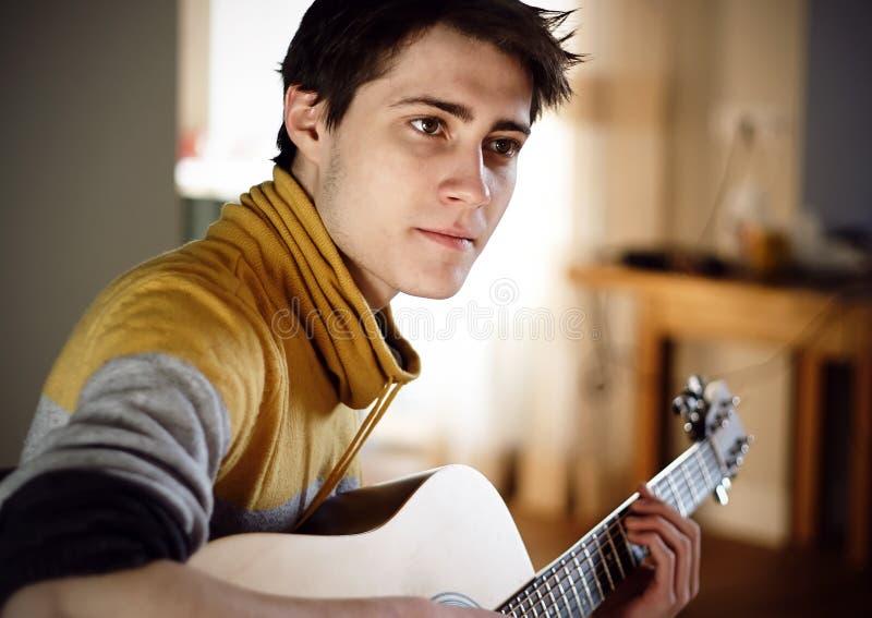 Tipo in chitarra acustica gialla dei giochi del maglione mentre sedendosi a casa immagini stock libere da diritti