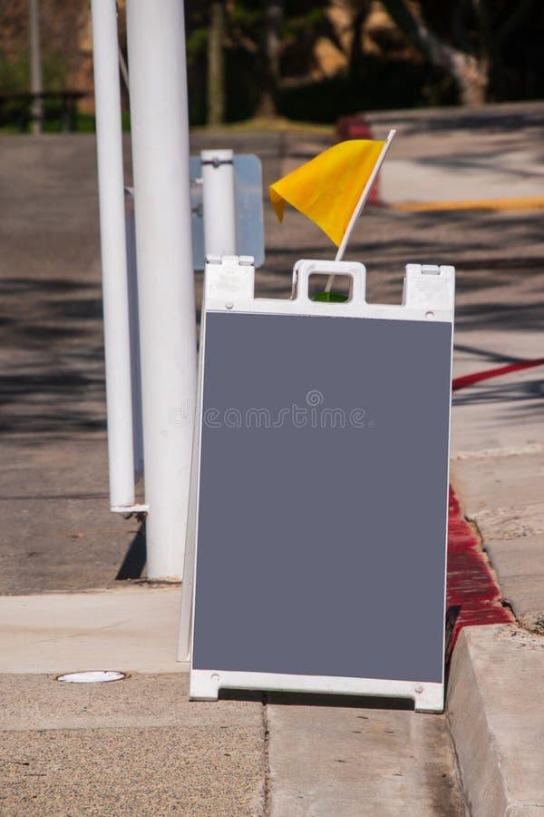Tipo cinzento vazio placa do sanduíche de giz em uma rua com uma bandeira amarela imagens de stock