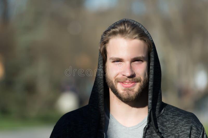 Tipo con il sorriso della barba in cappuccio il giorno soleggiato Maglietta felpata casuale barbuta di usura di uomo all'aperto S fotografia stock