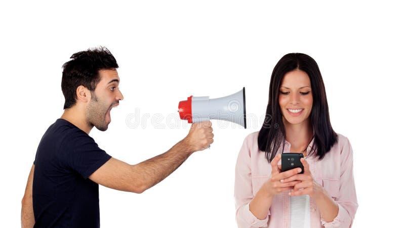 Tipo con un megafono che grida la sua amica con un cellulare fotografie stock