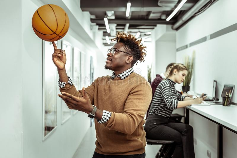 Tipo contento attivo con i dreadlocks che rotolano la palla di pallacanestro su un dito fotografie stock