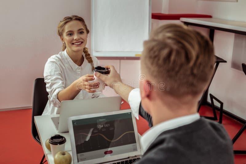 Tipo dai capelli corti generoso che propone il suo caffè in tazza del cartone alla donna sorridente fotografia stock libera da diritti