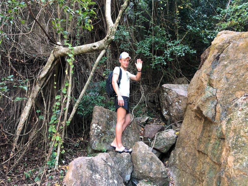 Tipo dalla carnagione chiara in vestiti della spiaggia sui precedenti di attaccatura delle rocce uniche dell'isola della Tailandi fotografie stock libere da diritti