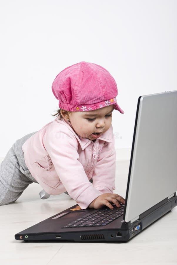 Tipo de arrastre feliz del bebé en la computadora portátil fotos de archivo libres de regalías