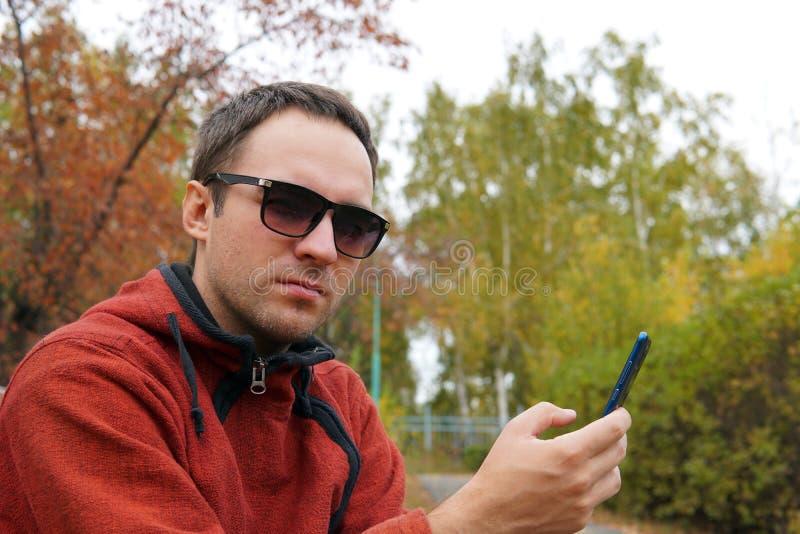 Tipo dei pantaloni a vita bassa che per mezzo del dispositivo all'aperto, ritratto all'aperto dello smartphone di giovane uomo al immagine stock