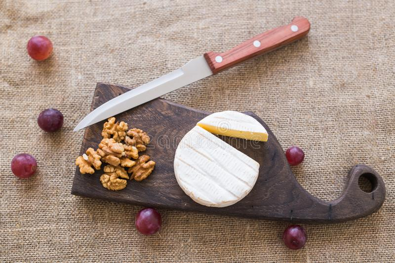 Tipo del brie de queso Queso del camembert Queso fresco del brie en un tablero de madera con las nueces y las uvas Queso italiano fotos de archivo