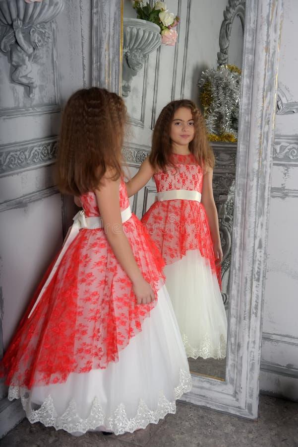 Tipo del este la muchacha la morenita en blanco con un vestido elegante rojo fotografía de archivo