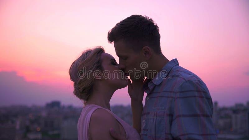 Tipo delicatamente e animatamente baciando la sua amica, abbracciante la appassionato, desiderio immagini stock libere da diritti