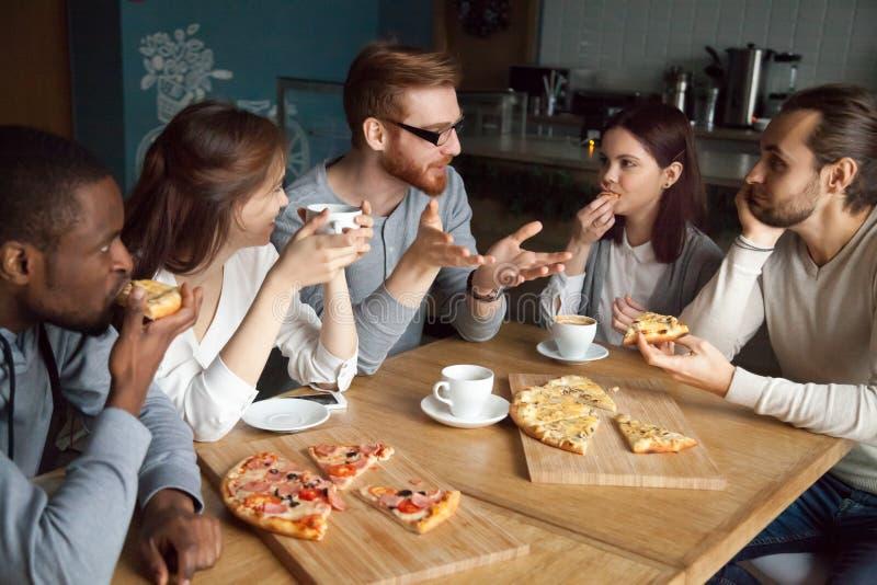 Tipo della testarossa che parla con diversi amici che mangiano pizza in pizzeria fotografia stock
