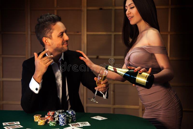 Tipo di bellezza che flirta con una ragazza che versa il champagne alla mazza fotografia stock libera da diritti
