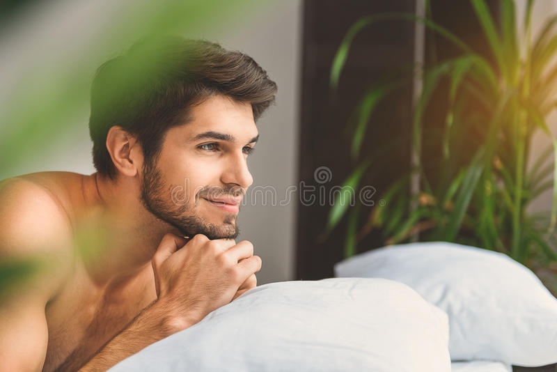 Tipo di Dreamful che si rilassa nella camera da letto immagini stock libere da diritti
