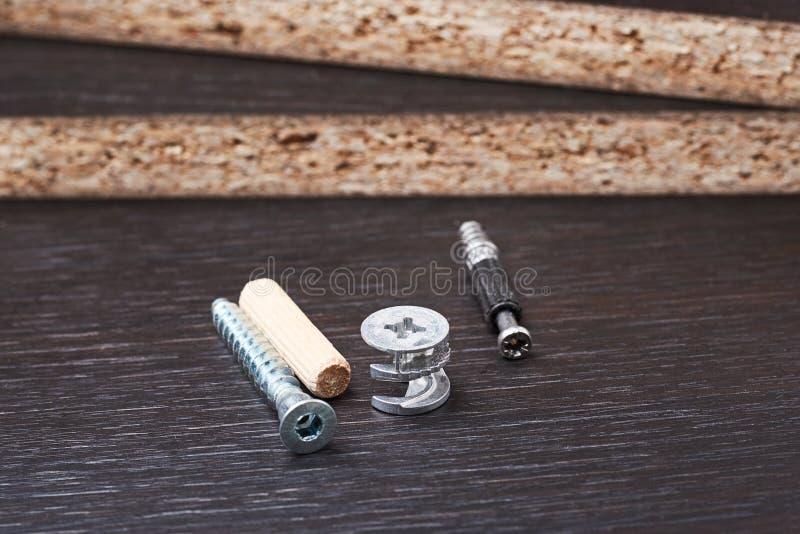 Tipo diferente do parafuso das ferramentas do conjunto da mobília, o excêntrico e o euro- em um fundo de madeira fotografia de stock