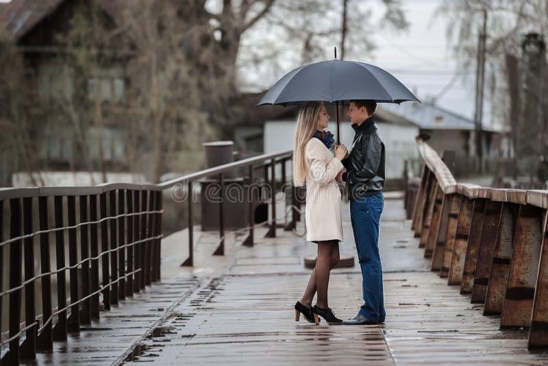 Tipo e la ragazza sotto un ombrello sul ponte fotografia stock