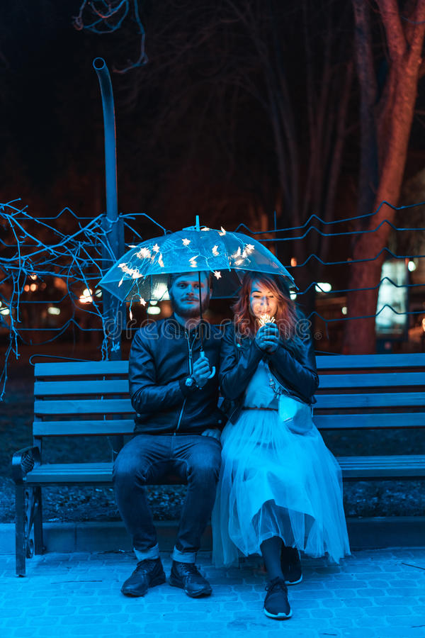 Tipo e ragazza che si siedono su un banco sotto un ombrello immagini stock