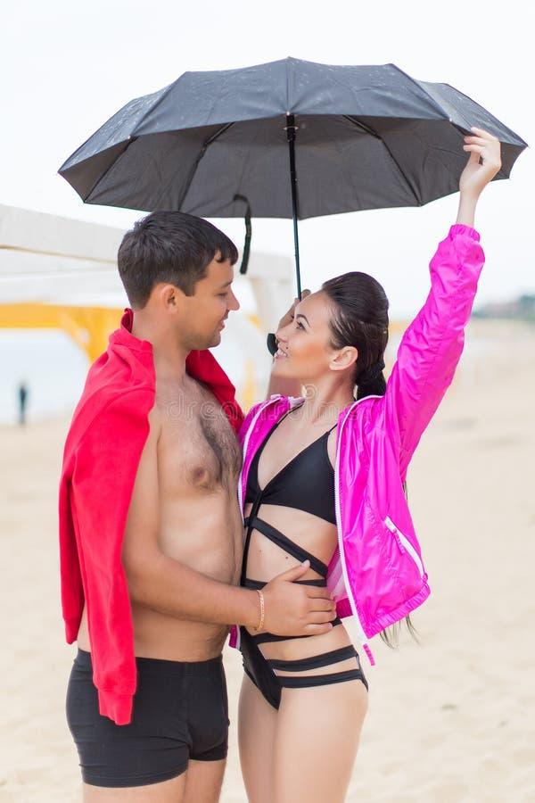 Tipo e ragazza sulla spiaggia di sabbia un giorno piovoso fotografie stock libere da diritti