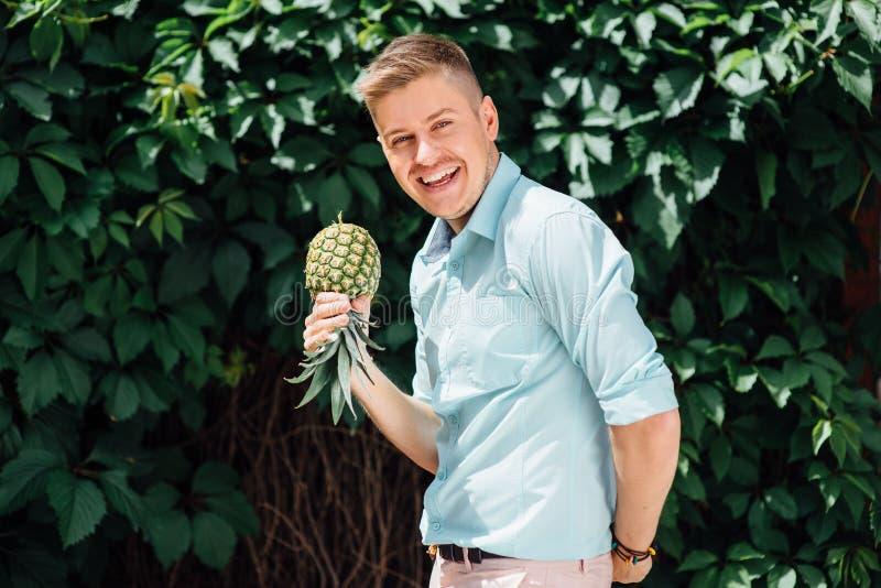 Tipo emozionale allegro che tiene un ananas fotografie stock