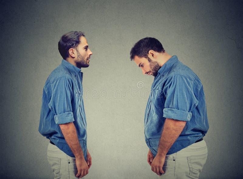 Tipo esile che esamina uomo grasso egli stesso Concetto di scelta di dieta immagini stock libere da diritti