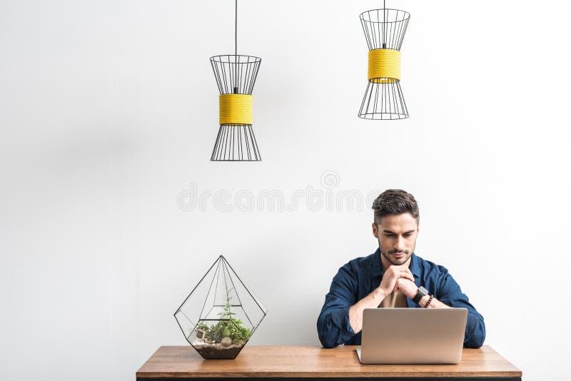 Tipo giovanile severo che usando la sua stanza del computer a casa fotografie stock libere da diritti