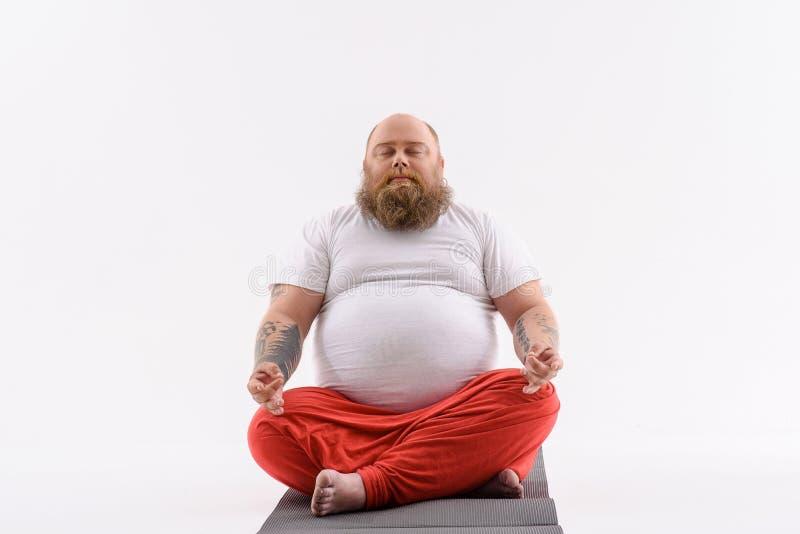 Tipo grasso calmo che fa yoga fotografia stock