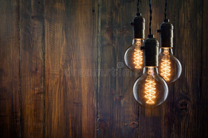 Tipo incandescente bulbos de Edison do vintage no fundo de madeira fotos de stock royalty free