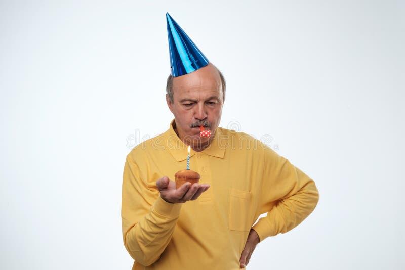 Tipo infelice di compleanno in maglietta gialla e cappuccio blu che stanno sulla torta di compleanno bianca della tenuta del fond immagine stock