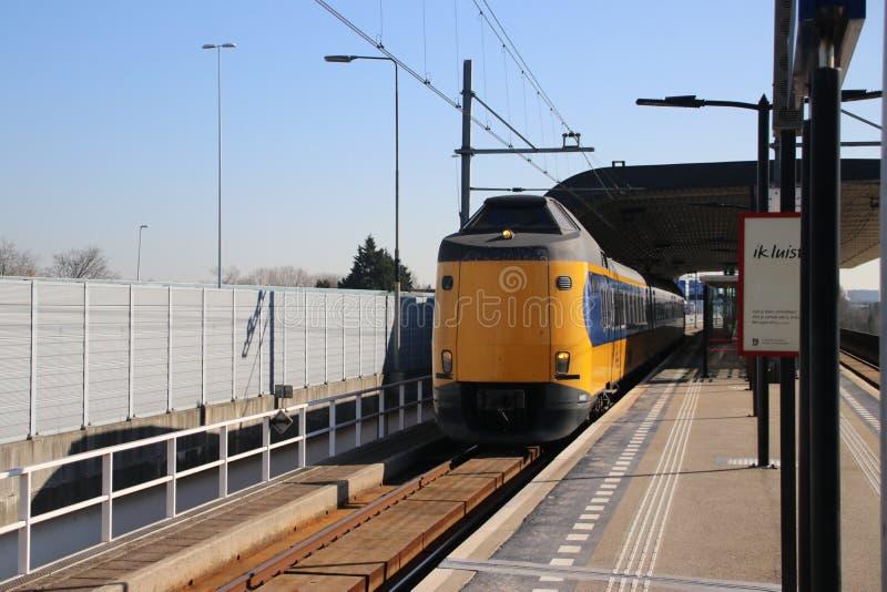 Tipo interurbano koploper del treno del ICM lungo il binario alla stazione ferroviaria Voorburg nei Paesi Bassi fotografia stock libera da diritti