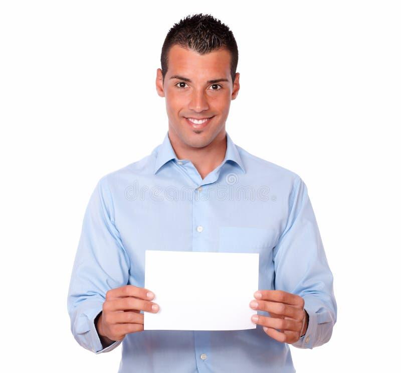 Tipo latino attraente che tiene una carta bianca fotografia stock libera da diritti