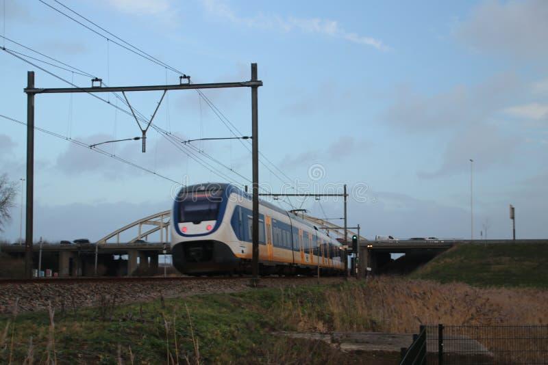 Tipo ligero local SLT del tren del communter del carril en la vía de ferrocarril entre el Gouda y La Haya en la travesía de Moord foto de archivo