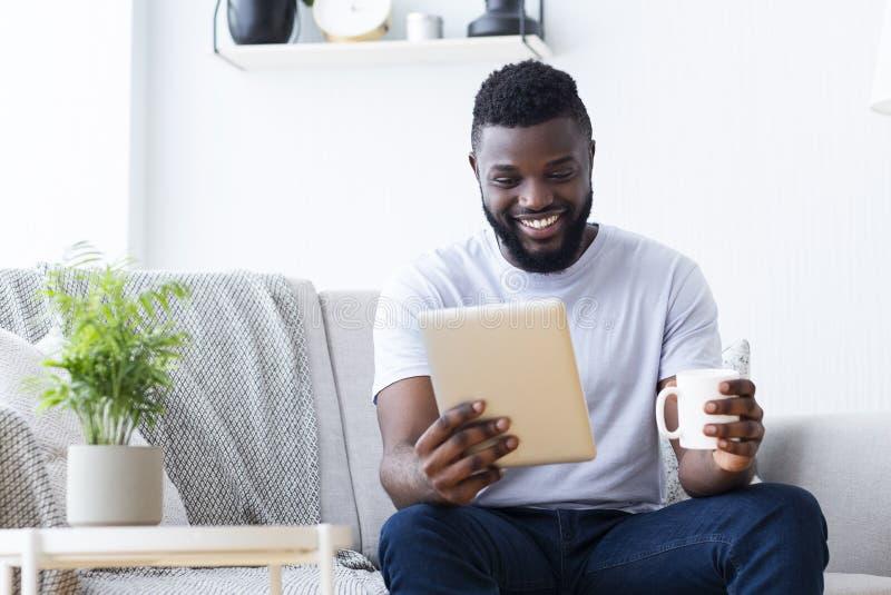 Tipo millenario africano che gode del caffè e delle notizie di mattina sulla compressa digitale fotografie stock