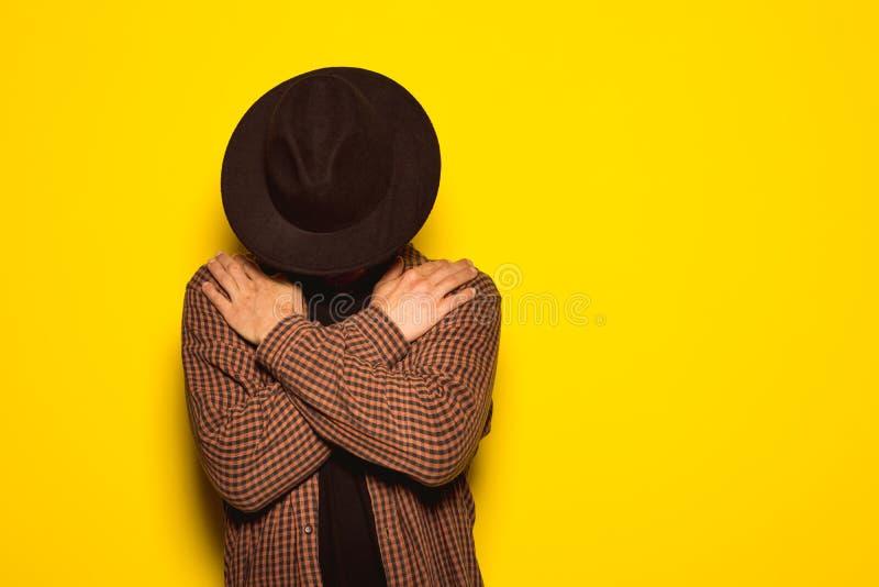 Tipo moderno e bello con un black hat su un fondo giallo fotografia stock libera da diritti