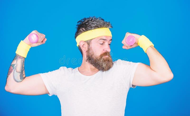 Tipo motivato dell'atleta Addestramento dello sportivo con il fondo blu delle teste di legno Migliori i vostri muscoli Atleta bar fotografia stock
