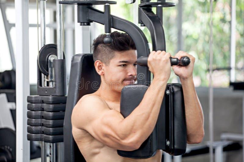 Tipo muscolare del culturista che fa esercizio pesante per il petto I immagine stock