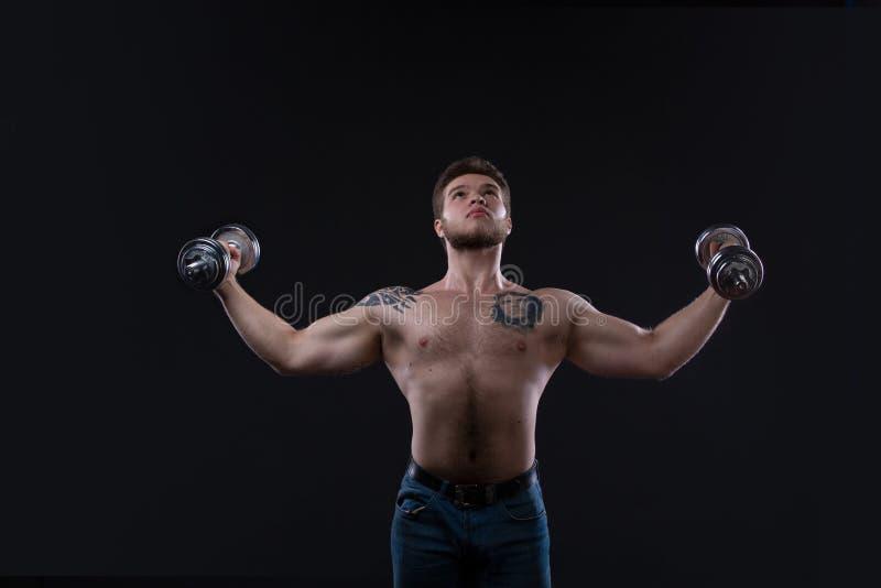 Tipo muscolare del culturista che fa gli esercizi con le teste di legno sopra fondo nero fotografie stock