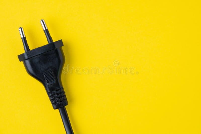 Tipo negro conector de enchufe eléctrico de C en fondo amarillo con c imágenes de archivo libres de regalías