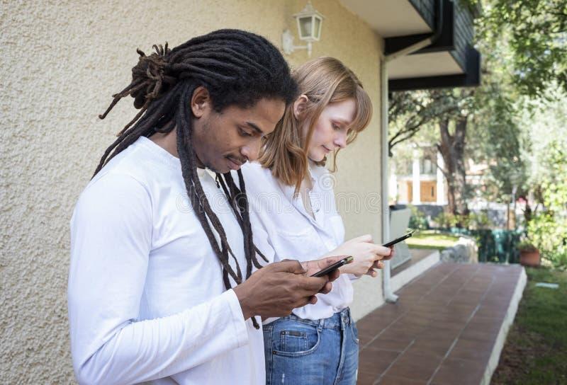 Tipo nero e ragazza caucasica che guardano e che chiacchierano con il telefono cellulare fotografie stock libere da diritti