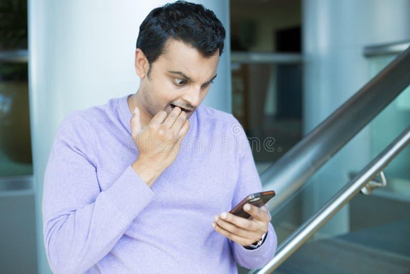 Tipo nervoso che vede cattive notizie sul telefono immagini stock