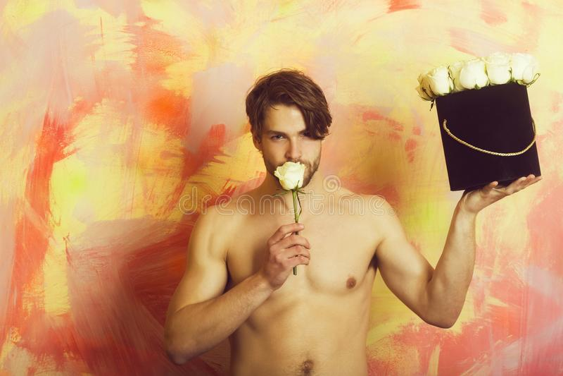 Tipo o uomo bello che annusa la rosa di bianco fotografia stock libera da diritti